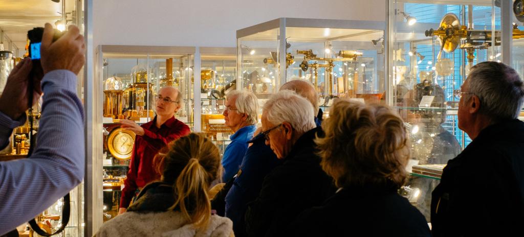 Prof. Franz Sachslehner (links) erläutert den Besuchern der Matinee die historischen physikalischen Geräte. Rechts oben sind Polarisationsapparate zu sehen. Dieser Ausstellungsraum befindet sich neben dem Christian-Doppler-Hörsaal.