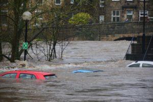 Eine Straße, Autos und Häuser stehen unter Wasser.