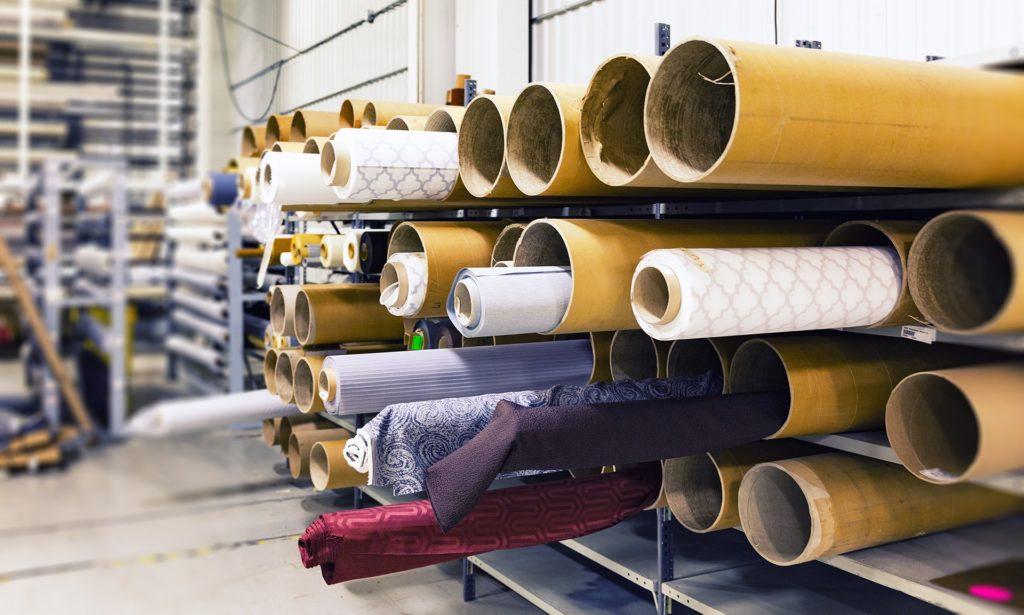 Rollen mit unterschiedlich gefärbtem Stoff liegen auf einem Regal in einer Fabrikshalle.