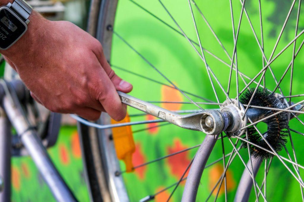 Eine Hand hält einen Schraubenschlüssel an einen Fahrradreifen.