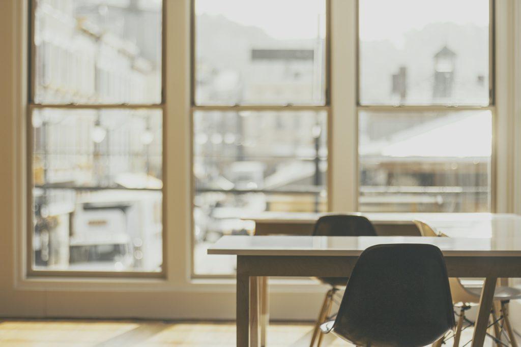 Zwei leere Schreibtische vor einer großen Fensterwand.