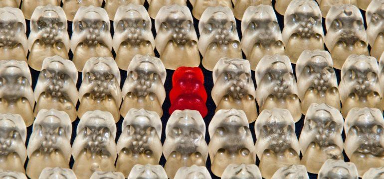 Ein rotes Gummibärchen zwischen weißen Gummibärchen.