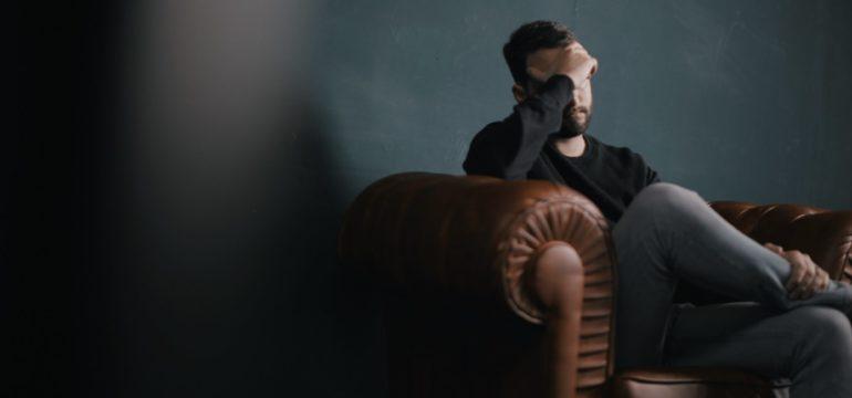 Ein Mann sitzt auf seinem brauen Sofa und schaut sehr gestresst aus.