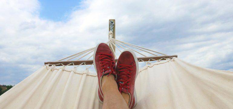 Füße in roten Schuhen auf einer weißen Hängematte vor blauem Himmel.