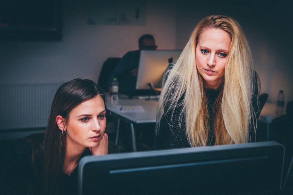 Eine dunkelhaarige und eine blonde Frau sehen auf denselben Computerbildschirm. Im Hintergrund sitzt ein Mann ebenfalls an einem Computer.