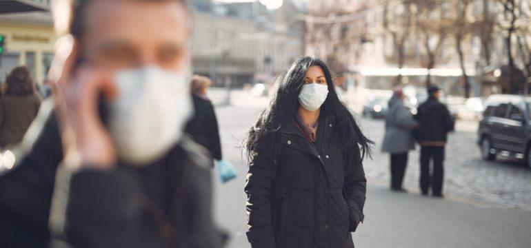 Ein Frau mit langer Winterjacke trägt eine Maske