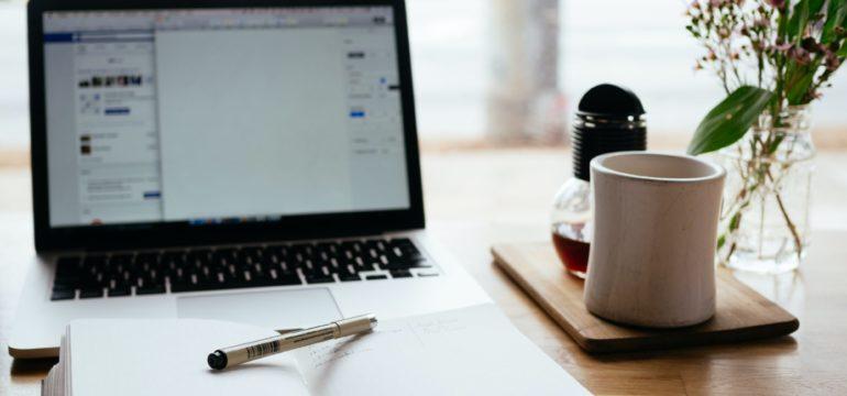 Offenes Notizbuch mit Stift liegt vor dem Laptop.