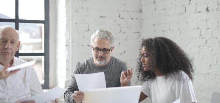 Zwei Männer und eine Frau prüfen Unterlagen.