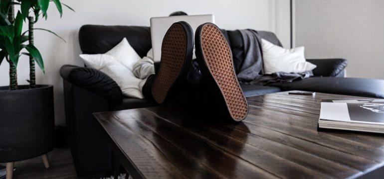 Ein Mann mit ausgestreckten Beinen arbeitet vom Wohnzimmertisch.