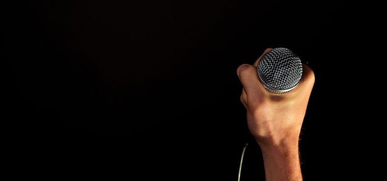 Ein Mann hält das Mikrofon.