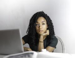 Eine schwarz gelockte Frau schaut seriös in die Kamera.