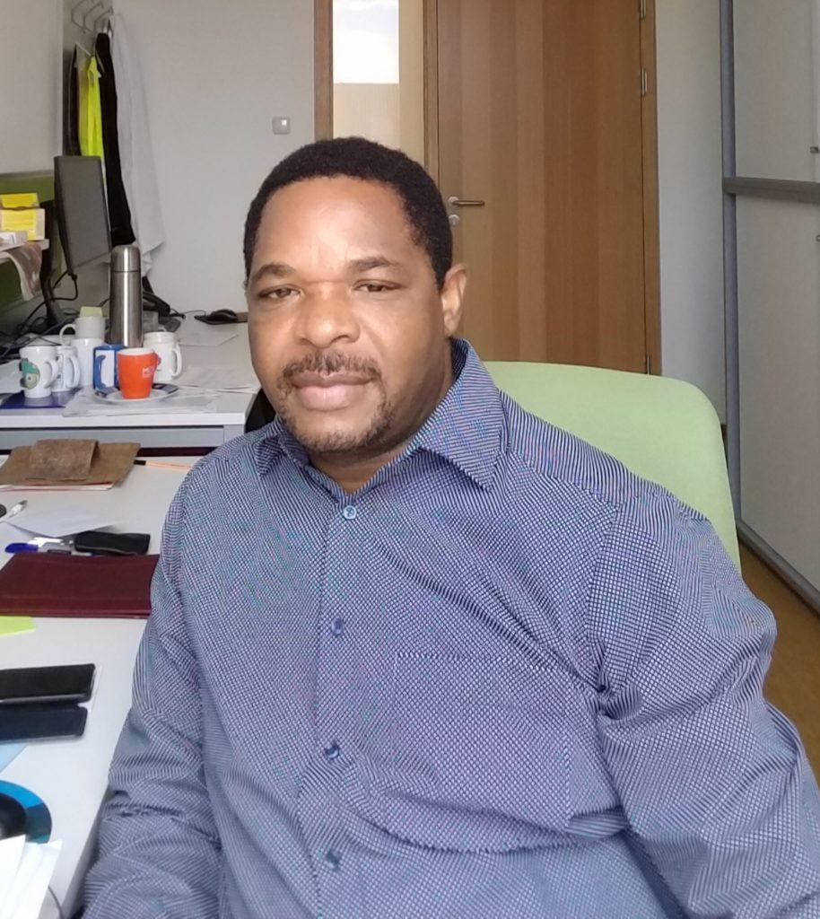 Dr. Gibron Nyanhongo sitzt in einem Büro auf einem grünen Bürosessel. Er trägt ein blaues Hemd und blickt direkt in die Kamera.
