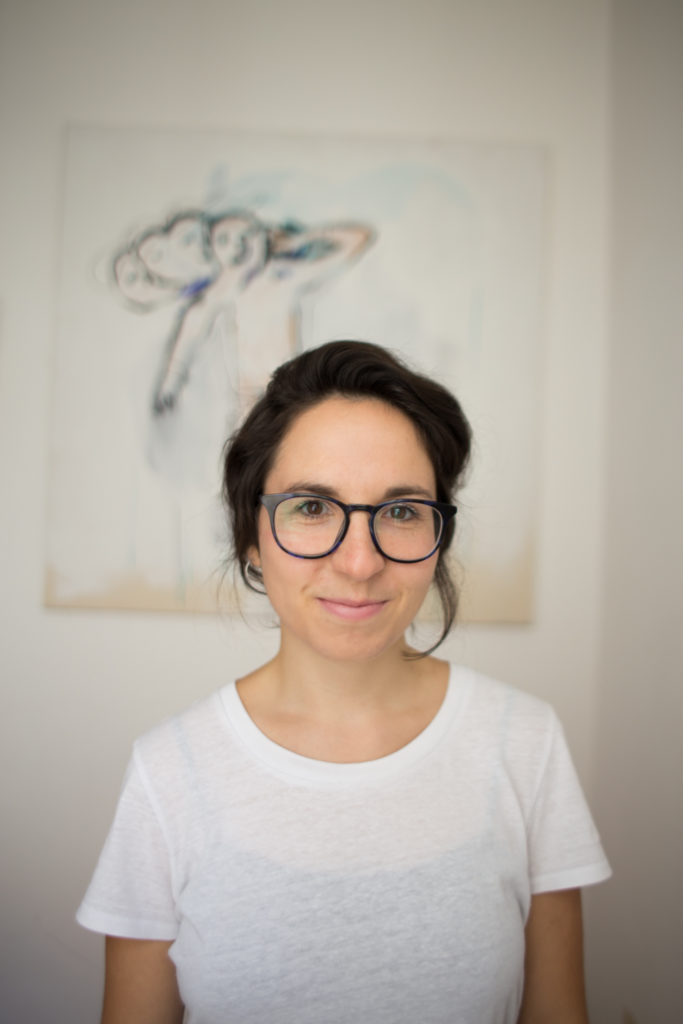 Ein Porträt-Foto von Dr. Julia Grillmayr vor einem Gemälde. Sie trägt eine schwarze Brille und ein weißes T-Shirt und lächelt in die Kamera.