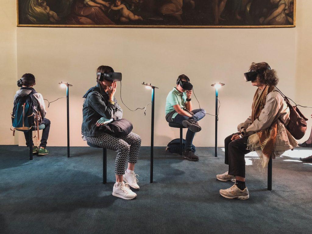 Vier Menschen sitzen in einer Kunstausstellung und tragen Virtual Reality Brillen.