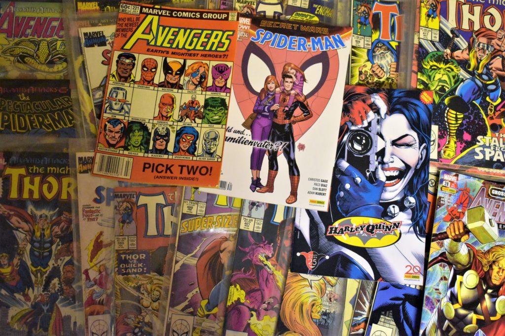 Mehrere Comic-Hefte von den Avengers, Spider Man und anderen Serien liegen nebeneinander.