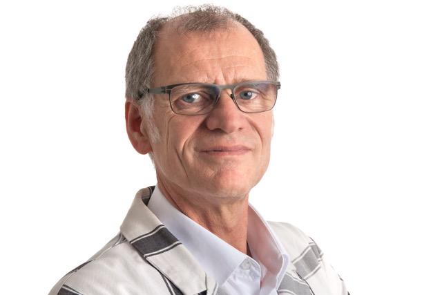 Porträtfoto von Willi Haas. Er trägt ein kariertes Jackett und eine Brille und blickt direkt in die Kamera.