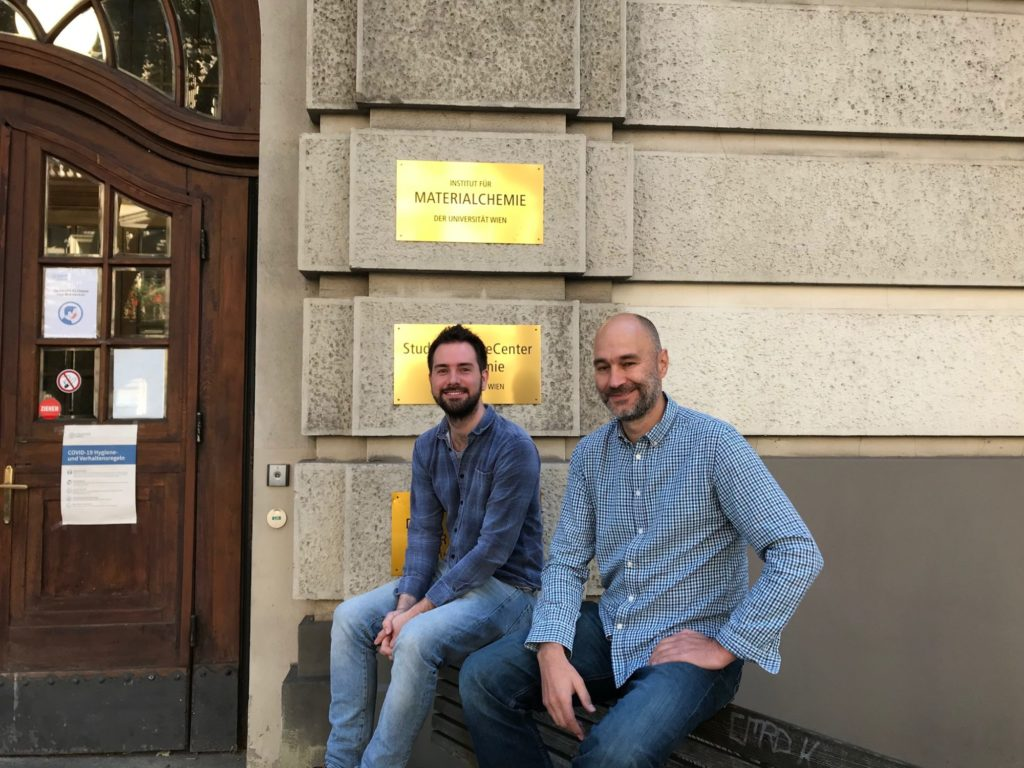 Mitchell Jones und Alexander Bismarck sitzen vor dem Institut für Materialchemie. Beide tragen Jeans und blaue Hemden und lächeln in die Kamera.