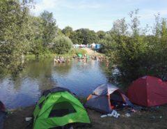 Am Ufer des Flusses stehen mehrere Zelte. Im Fluss sieht man ungefähr vierzig Menschen.