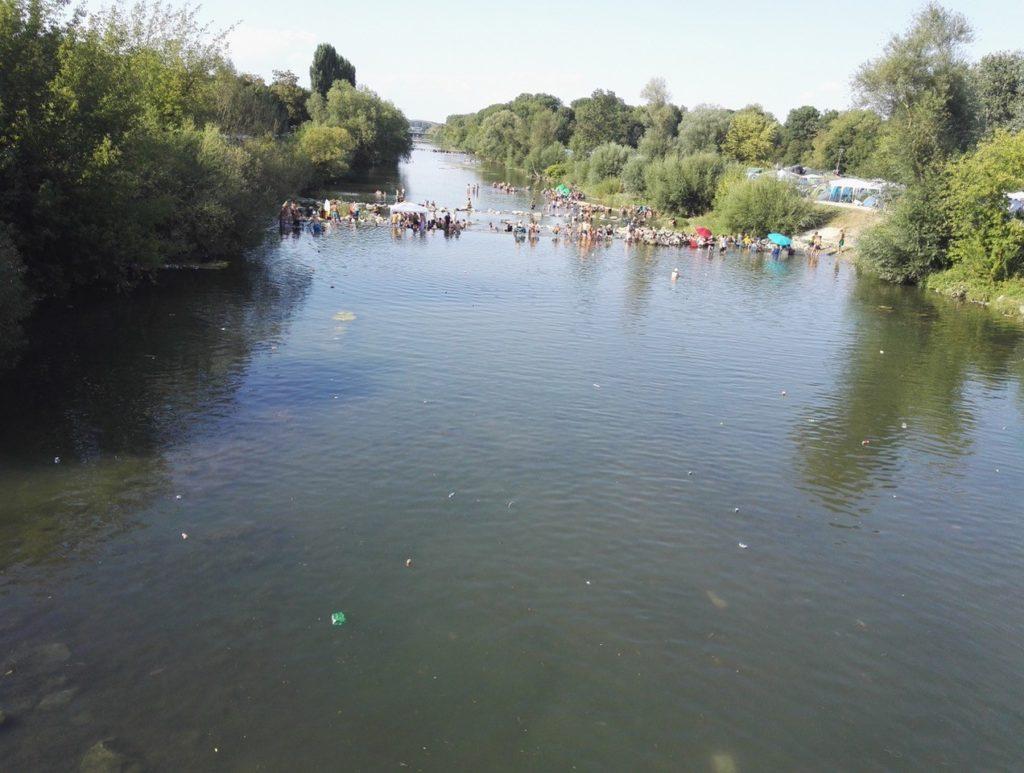 Ein gerader Blick den Fluss entlang, im Hintergrund vergnügen sich Menschen im Wasser. An den Ufern des Flusses stehen Bäume und Sträucher.