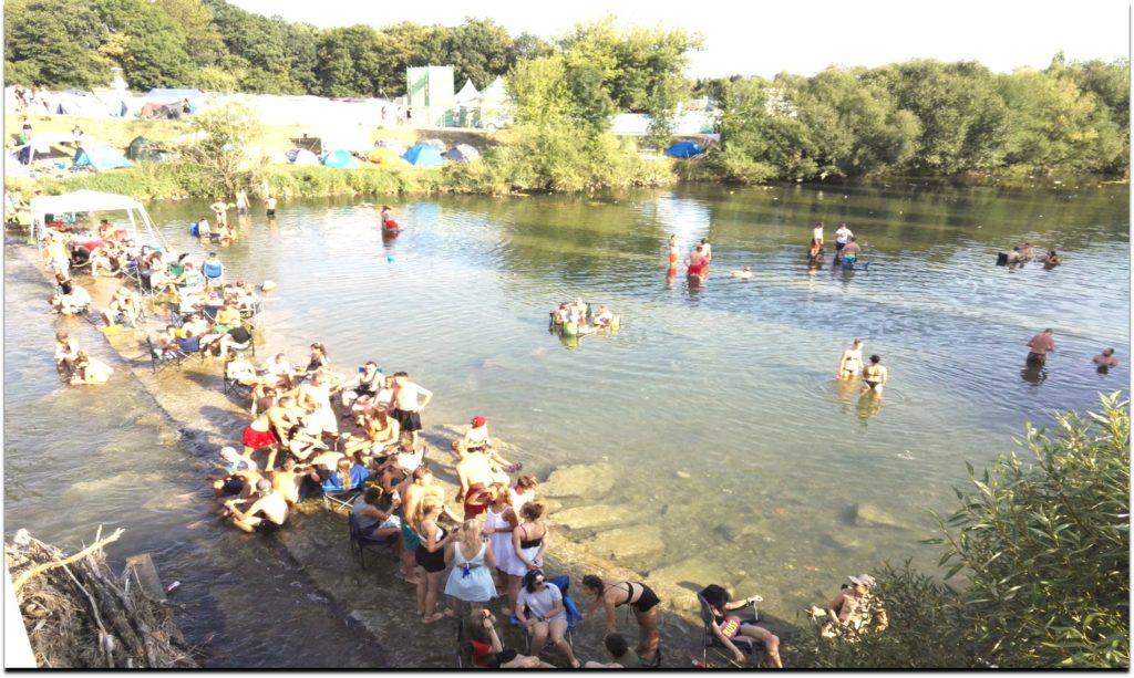 Viele Menschen stehen und sitzen im Fluss.
