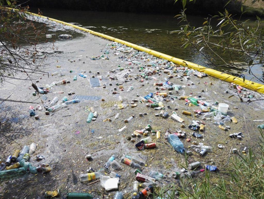 Eine gelbe Absperrung im Fluss hält eine Menge Müll davon ab, weiter zu fließen.
