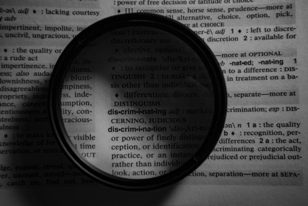 """Eine Lupe liegt über dem Wort """"discrimination"""" in einem Wörterbuch."""