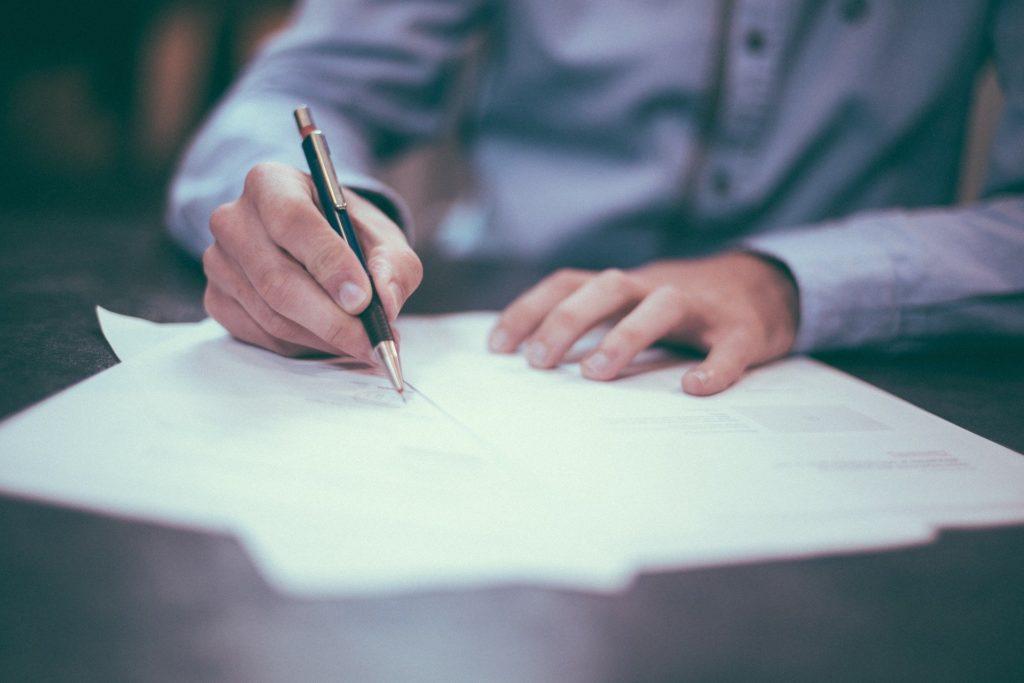Eine Person in einem hellblauen Hemd schreibt mit einem Kuli auf Papier. Das Gesicht der Person ist nicht zu sehen.