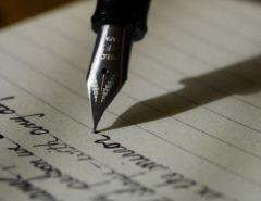 Eine Füllfeder schreibt mit schwarzer Tinte auf liniertem Papier.