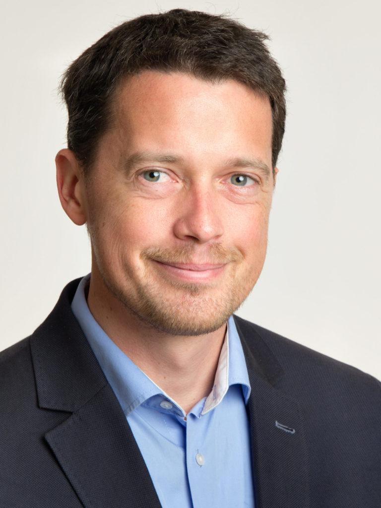 Ein Porträtfoto von Stefan Rass in einem dunklen Anzug vor einem hellgrauen Hintergrund.