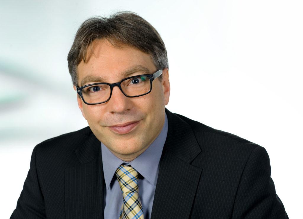 Ein Porträtfoto von Thomas Stegemann vor einem weißen Hintergrund, er trägt einen Anzug und eine Brille.