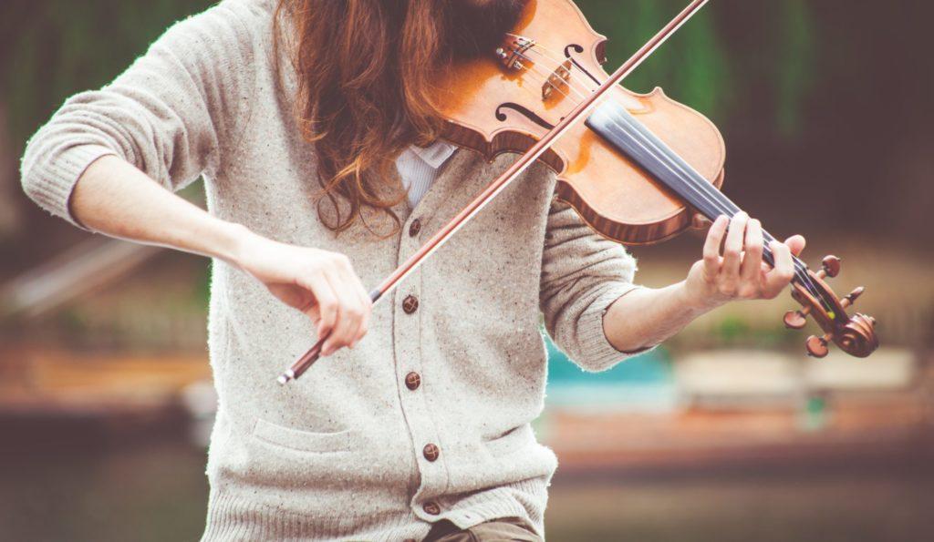 Eine Person spielt draußen Geige.