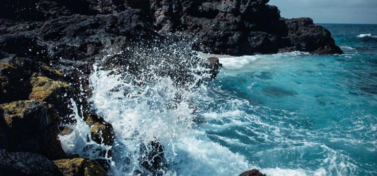 Meeresbrandung schlägt gegen Felsen.