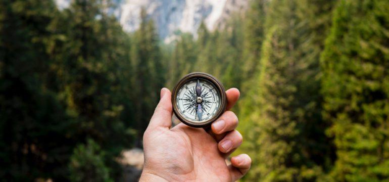 Eine Hand hält einen Kompass vor einem Bergpanorama.