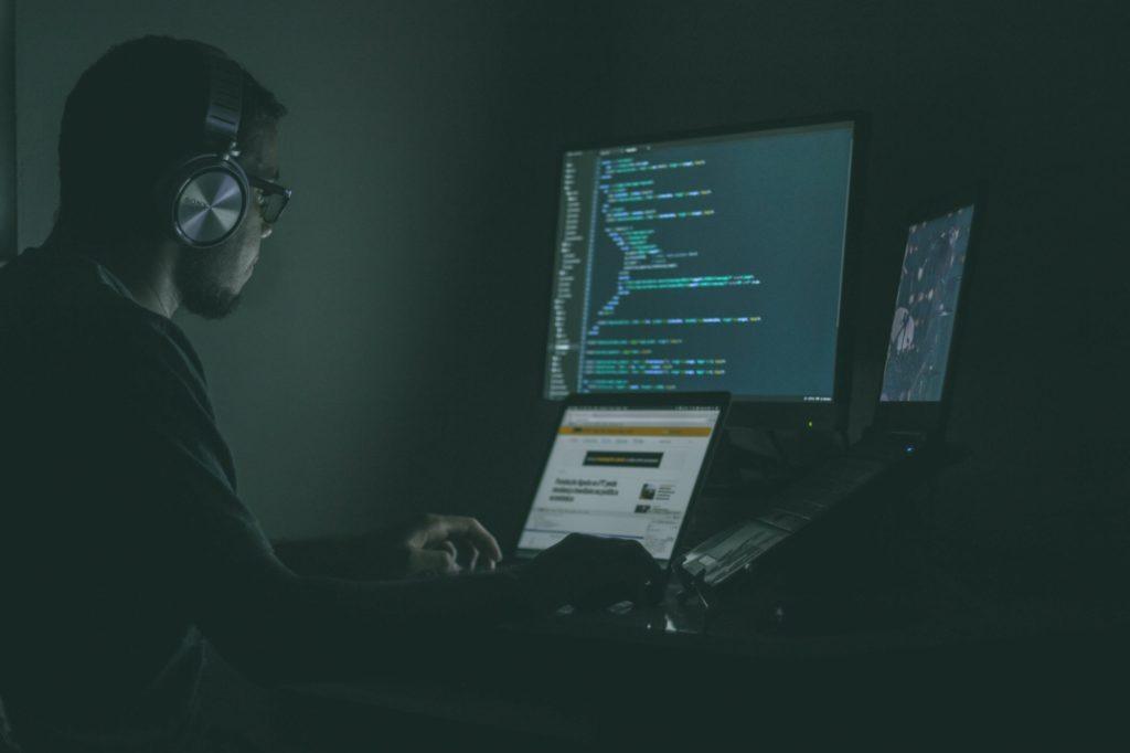 Eine Person mit Kopfhörern sitzt im Dunkeln vor mehreren Bildschirmen, die einen Code anzeigen.