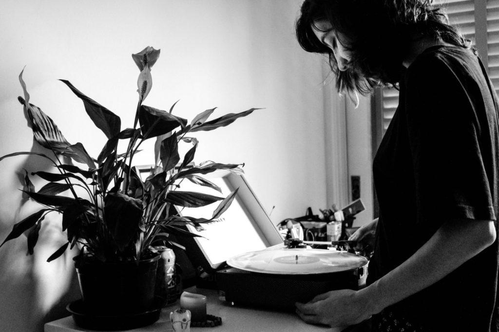 Schwarz-Weiß-Foto von einer Person vor einem Plattenspieler.