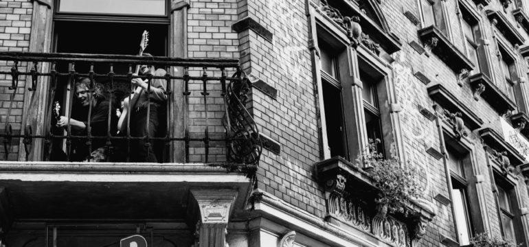 Schwarz-Weiß-Foto von zwei Musiker*innen, die auf einem Balkon Gitarre spielen.
