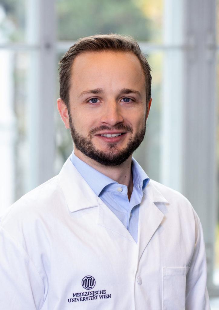 Ein Porträtfoto von Emir Benca, der einen weißen Labormantel mit dem Logo der Medizinischen Universität Wien trägt.