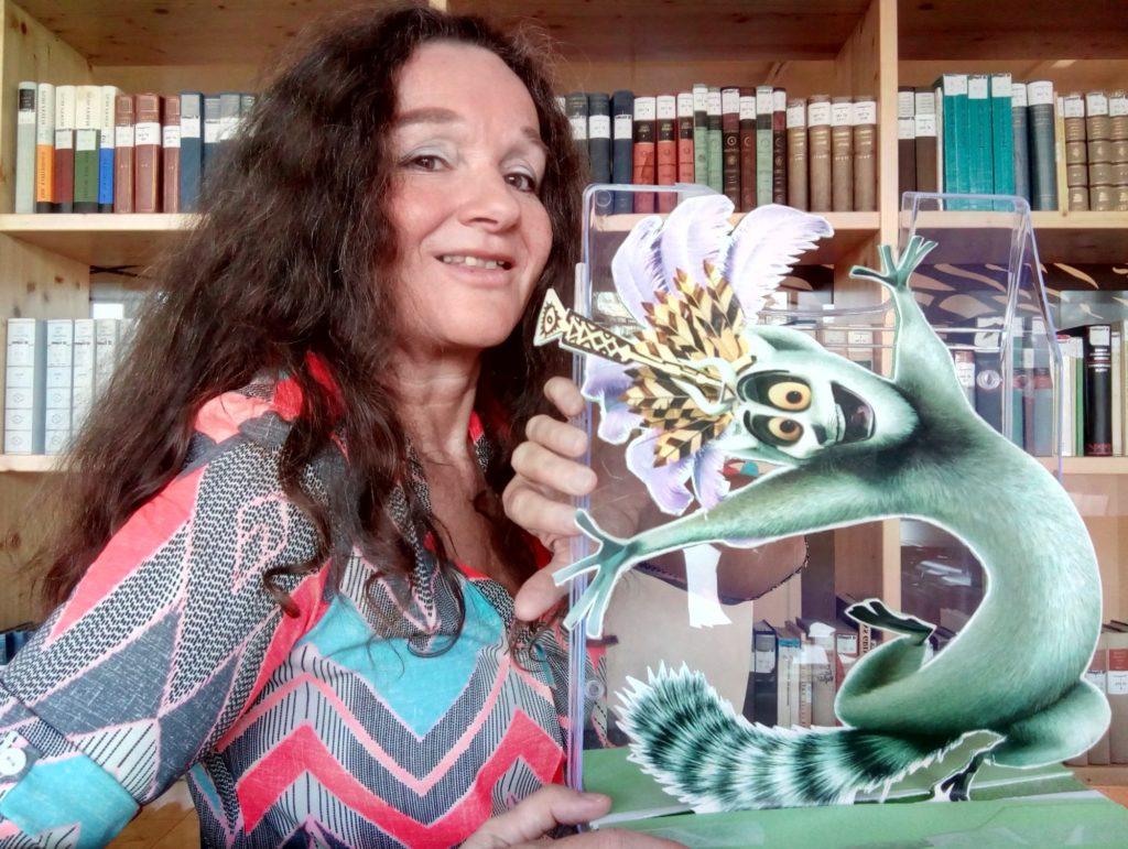 Gerda Moser steht für einem Bücherregal und hält ihr Büromaskottchen, einen Ausdruck von King Julien aus dem Film Madagascar, in die Höhe.