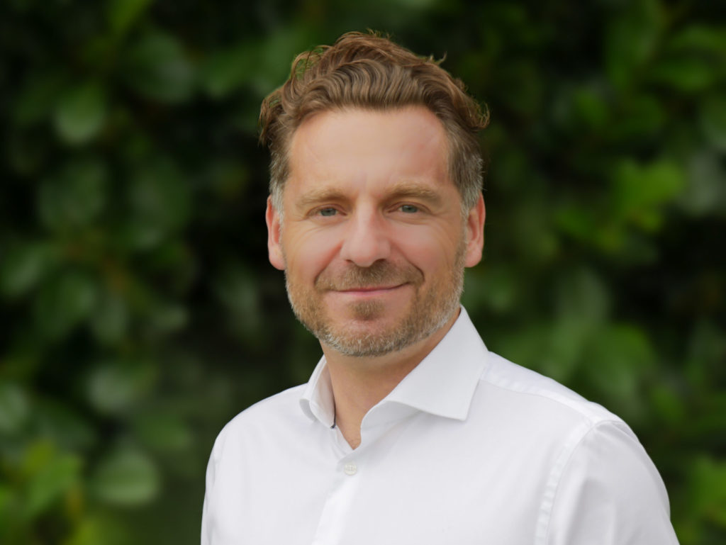 Porträtfoto von René Riedl, der ein weißes Hemd trägt und vor einem grünen Hintergrund in die Kamera lächelt.