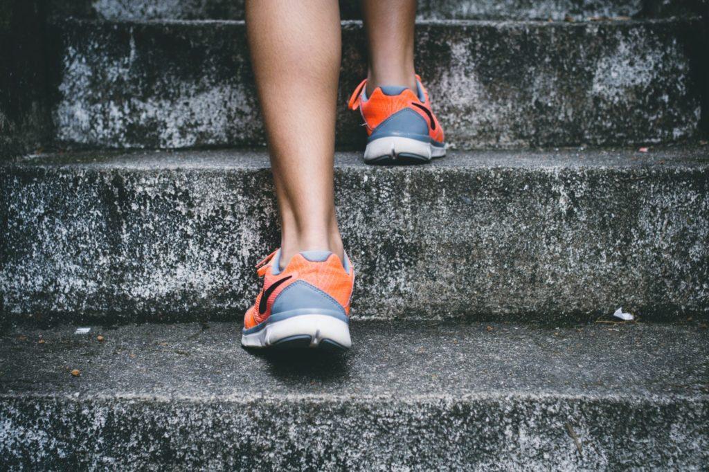 Das Bild zeigt zwei Füße einer Person in Laufschuhen, die eine Treppe hinauflaufen.