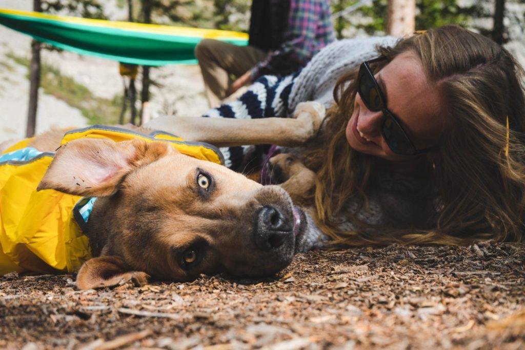 Ein Hund und eine Person mit langen Haaren und einer Sonnenbrille liegen nebeneinander am Boden.