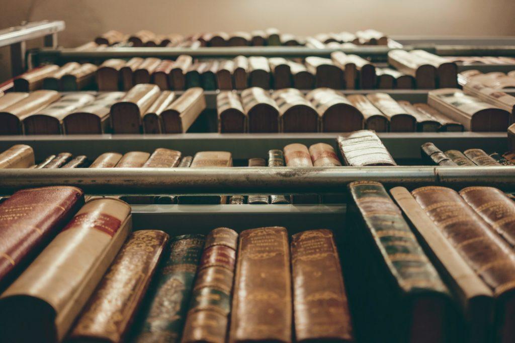 Das Bild zeigt ein Regal voller alter Bücher, schräg von unten fotografiert.