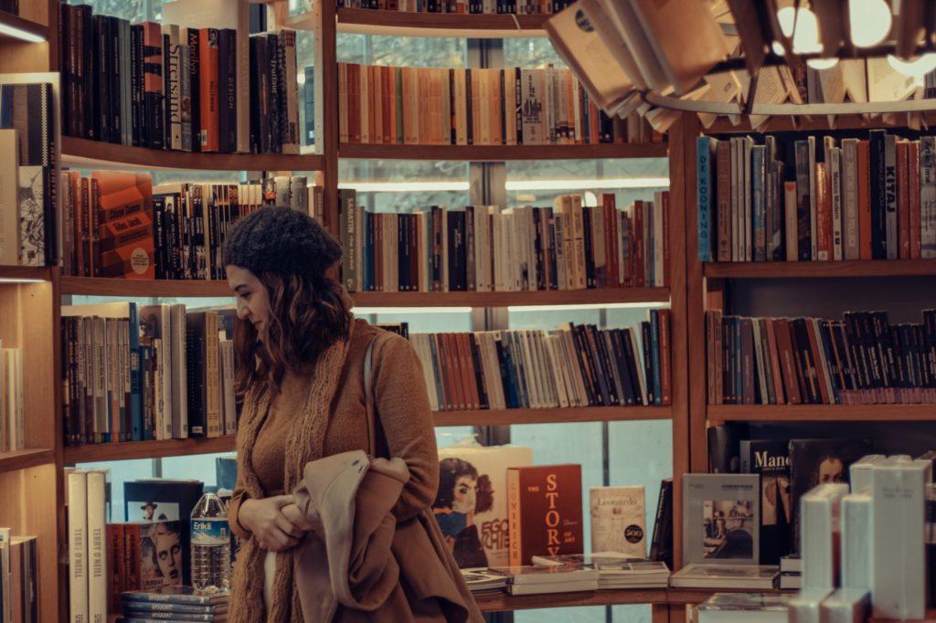 Ein Person sieht sich Bücher in einem Buchladen an. Sie trägt einen braunen Mantel, eine Strickmütze und hat lange Haare.