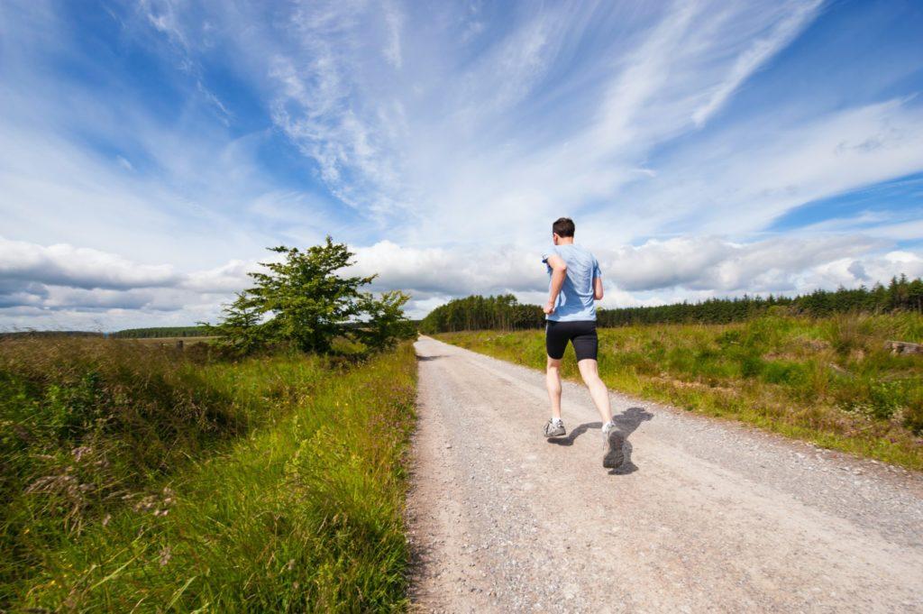 Eine Person in schwarzen Shorts und einem hellblauen T-Shirt läuft einen Weg zwischen zwei Wiesen entlang.