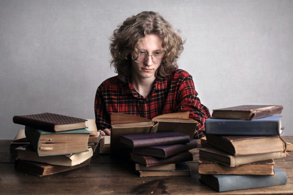 Eine Person mit Locken und einer Brille sitzt an einem Tisch vor Stapeln alt aussehender Bücher.