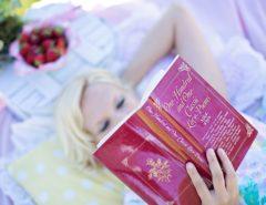 """Eine Person mit blonden Haaren liegt auf einer Picknickdecke und liest ein Buch mit dem Titel """"One Hundred and One Classic Love Poems""""."""