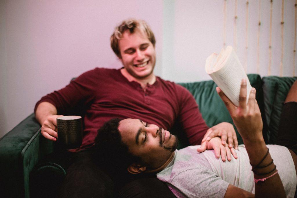 Zwei männlich lesbare Menschen liegen auf einer Couch. Einer liegt mit dem Kopf auf dem Schoß des anderen und liest in einem Buch.