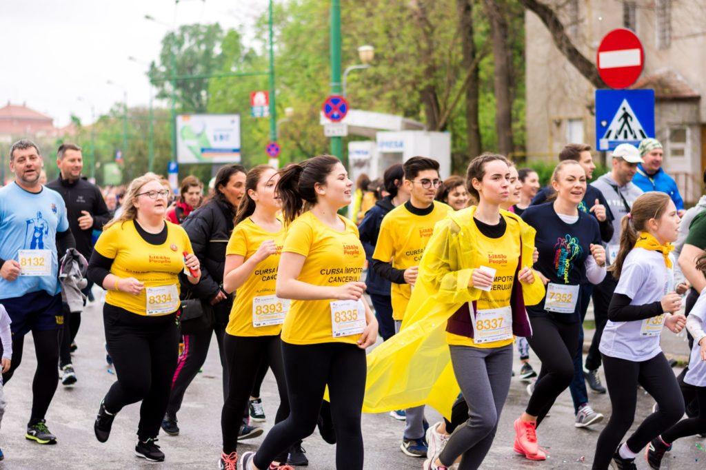 Eine Gruppe Menschen von Menschen laufen bei einem Wettkampf. Sie tragen Startnummern mit gelben Ziffern.