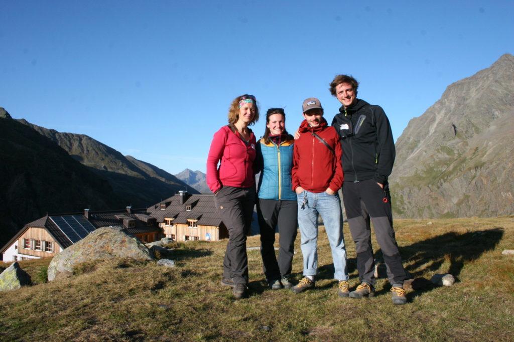 Das Forschungsteam der Uni Innsbruck (vier Personen) steht auf einem Hügel, im Hintergrund sieht man Berge und eine Hütte.