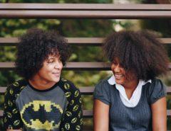 Zwei Personen mit dunklen, krausen Haaren sitzen auf einer Bank und sehen einander an.